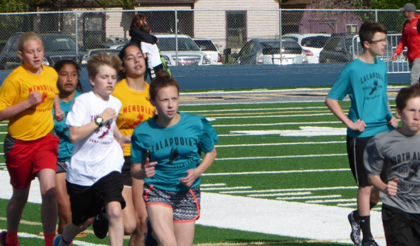Students running at middle school track meet.